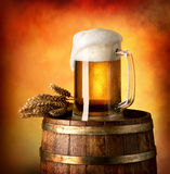 Lager on barrel. Glass of lager and wheat on a wooden barrel stock photography