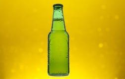 Lager beer. Green bottle.  on yellow bokeh background Stock Image