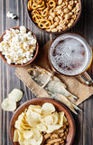 Lager beer glasses and snacks on wooden table. Nuts and dry fish Royalty Free Stock Photo