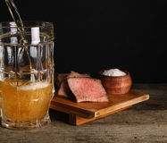 Lager beer with meat snack to beer. Beer poured into glass close up on dark background. Lager beer with meat snack to beer Royalty Free Stock Photo