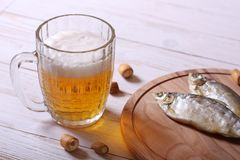 Lager beer mug and snacks on white wooden table. royalty free stock image