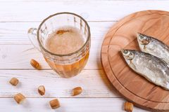 Lager beer mug and snacks on white wooden table. stock image
