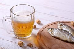Lager beer mug and snacks on white wooden table. royalty free stock photos