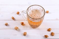 Lager beer mug and snacks on white wooden table. stock photo
