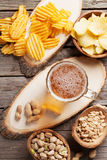 Lager beer mug and snacks. On wooden table. Nuts, chips. Top view stock image