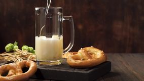Lager beer is pouring into a mug. Light beer on a dark wooden table. Lager beer is pouring into a mug. Light beer on a dark wooden table and german pretzels stock video footage
