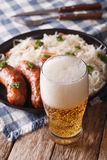 Lager beer and sauerkraut with sausage close-up. Vertical Stock Photography