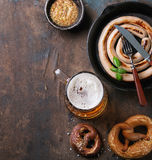Lager beer with sausage and pretzels Stock Images