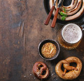 Lager beer with sausage and pretzels Stock Photos