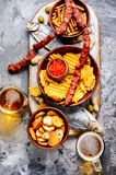 Lager beer and snacks. Beer and snacks.Chips, fish, beer sausages on the table stock photography