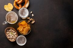 Lager beer and snacks. On stone table. Nuts, chips, pretzel. Top view with copy space royalty free stock photos