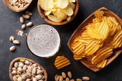 Lager beer and snacks on stone table. Nuts, chips. Top view Stock Images
