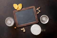Lager beer and snacks. On stone table. Nuts, chips. Top view with chalkboard for copy space royalty free stock images