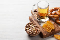 Lager beer and snacks. On wooden table. Nuts, chips, pretzel. With copy space stock images