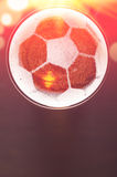 Lager beer on table. Soccer or football ball symbol on foam of fresh lager beer glass on black table, view from above Stock Images