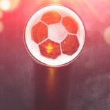 Lager beer on table. Soccer or football ball symbol on foam of fresh lager beer glass on black table, view from above Royalty Free Stock Photos