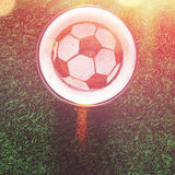 Lager beer on table. Soccer or football ball symbol on foam of fresh lager beer glass on grass, view from above Stock Image