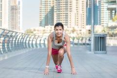 Lager begin De atleet stelt en maakt de training in werking Atletische vrouw Royalty-vrije Stock Fotografie