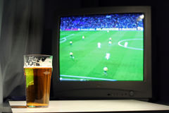 Lager and football on the tv. Pint of lager with soccer match on the tv as background royalty free stock images
