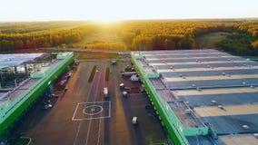 Lager mit Lastwagenn durch Hubschrauberstandort bei dem Sonnenaufgang von der Luft stock video footage