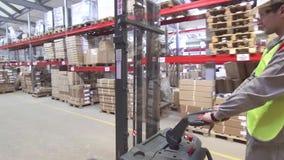 Lagerarbeitskraft auf dem Gabelstapler, der Fracht transportiert stock video