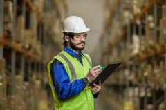 Lagerarbeitskraft, die Checkliste betrachtet Lizenzfreies Stockfoto