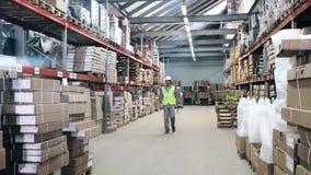 Lagerarbeitskraft-Schutzausrüstung geht durch Lager stock video footage