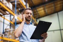 Lagerarbetare eller arbetsledare med en smartphone arkivbilder