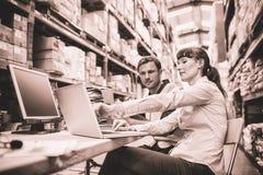 Lagerarbetare och chef som ser bärbara datorn arkivfoton