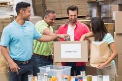 Lagerarbetare som packar upp donationaskar Arkivfoto