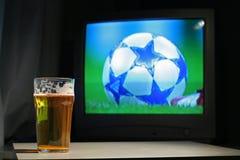 Lagerbier en voetbal op TV Royalty-vrije Stock Foto