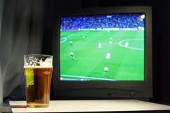 Lagerbier en voetbal op TV Royalty-vrije Stock Afbeeldingen