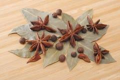 Lagerblad, kryddpeppar och stjärnaanis på en trätabell Fotografering för Bildbyråer