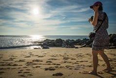 Lagere mening bij de jonge vrouw status op zandig strand die van Atlantische kust foto's van mooi zeegezicht en surfers nemen Royalty-vrije Stock Afbeelding