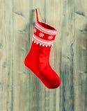 lagerföra för jul röd socka med vitt hänga för snöflingor Arkivfoton