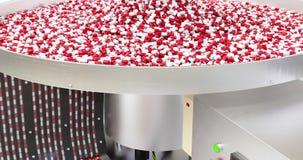 Lagerföra videoen, processen av produktion av preventivpillerar, minnestavlor, röd-vit kapslar stock video