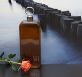 Lagerfeld, mensen` s geur, grote die parfumfles voor het beeld van een golfbreker in het overzees met Engelsen wordt verfraaid na stock afbeelding