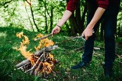 Lagerfeuer auf der Natur Mann `s Hände Brennholzvorbereitung für Feuer Stockbild