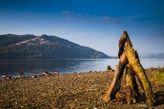 Lagerfeuer auf Ufer von See Stockfotos