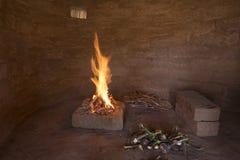 Lagerfeuer in der ursprünglichen Hütte des luftgetrockneten Ziegelsteines Stockbild
