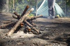 Lagerfeuer mit frischem Holz entflammt kaum, auf einem unscharfen Hintergrund steht eine Frau nahe einem Zelt und einem Wald lizenzfreie stockfotografie