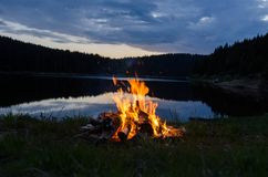 Lagerfeuer nach Sonnenuntergang in den Bergen nahe bei einem See stockfotografie