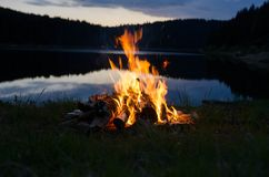 Lagerfeuer nach Sonnenuntergang in den Bergen nahe bei einem See stockbild