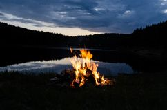 Lagerfeuer nach Sonnenuntergang in den Bergen nahe bei einem See lizenzfreie stockfotos