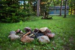 Lagerfeuergrube auf grünem Rasen mit einer Hängematte, die im Hintergrund - 1/2 hängt stockbild