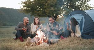 Lagerfeuerzeit für eine Gruppe Freunde, am Picknick mit Zelt und eine junge Familie mit ihrem Jungen, der zusammen herein spielt stock footage
