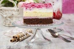 Lagerkaka med rosa isläggning på en glass kakaställning Royaltyfri Foto