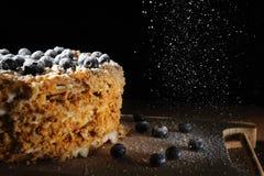 Lagerkaka Napoleon med bärblåbäret på ett grovt trämagasin, stänk med pudrad sockersvartbakgrund för menykafé Fotografering för Bildbyråer