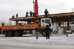 Laget av byggmästare som arbetar på konstruktionen av byggnaden i Novosibirsk, i vintern av hälld betong genom att använda en sak arkivbilder