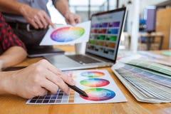 Laget av det idérika grafiska märkes- mötet som arbetar på nytt projekt, väljer valfärg och att dra på diagramminnestavlan med ar royaltyfri foto